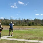 A group of skeet shooters on a field