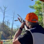 A sporting clays shooter firing at a clay pigeon